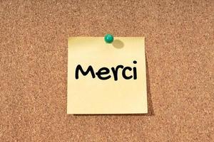 Merci - palabra de agradecimiento en idioma francés en nota amarilla sobre tablero de corcho foto