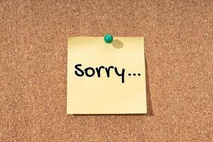 Lo siento palabra en nota amarilla en tablero de corcho foto
