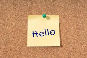 Hola palabra en nota amarilla en tablero de corcho foto
