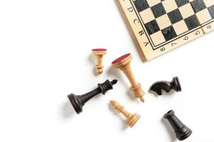 Flat lay composition with chess pieces and chessboard isolated on white background with copy space photo