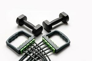 composition with two dumbbells and an expander on a white background photo