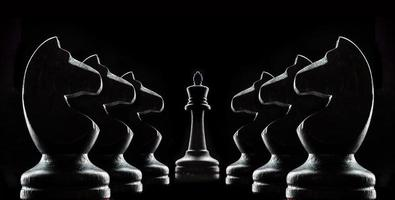 Silhouettes of chess on a black background photo