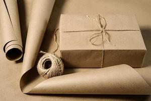 A box wrapped in craft paper a roll of paper and a skein of twine photo