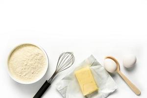 Harina huevos mantequilla batidor cuchara aislado sobre fondo blanco. foto
