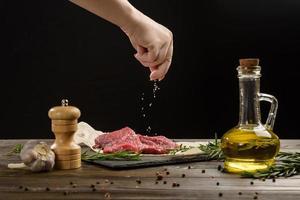 Hand sprinkle salt on beef steaks photo