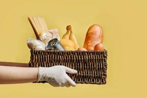 Wicker basket with a set of products in the hands in protective gloves isolated on a yellow background photo
