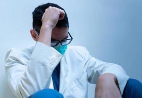 Retrato de joven médico caucásico en bata blanca que se siente estresado y tiene síndrome de agotamiento foto