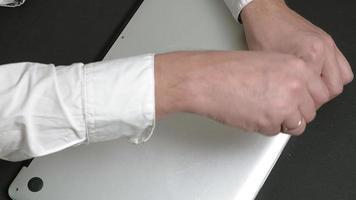 um homem remove a tampa de um laptop e examina o microcircuito do laptop com uma lupa video