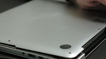 A man removes the lid of a laptop, close-up video
