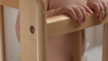 Close-up of baby hands holding on to the crib video