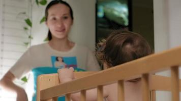 Woman playing with a baby beginner standing in a crib video