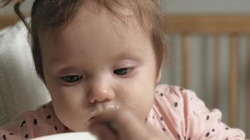 maman nourrit une petite fille dans une chaise haute video