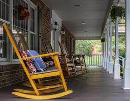 Rocking chairs lined up on long front porch photo