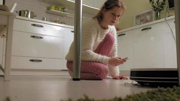 A young woman is vacuuming a robot video