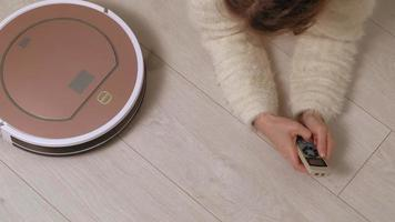 A young woman controls a robot with a vacuum cleaner video
