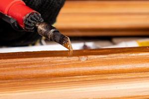 restauración y eliminación de defectos en una superficie de madera con cera caliente foto