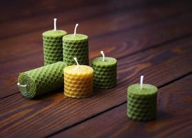 Beeswax candles on a dark wooden table photo