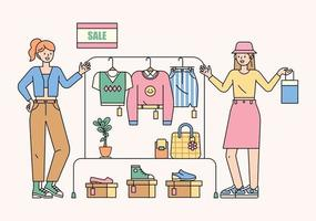 Girls are choosing fashion items and clothes in the sale section. flat design style minimal vector illustration.