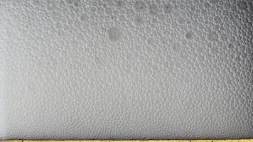 Macro of beer foam bubbles in a glass video