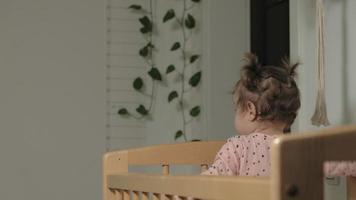Little cheerful girl in a baby crib video