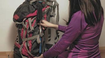 uma mulher com roupa térmica violeta prepara uma mochila para uma viagem de escalada video