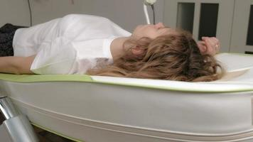 A woman lies on a massage electronic bed video