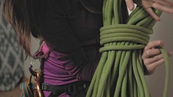 uma mulher com roupa térmica roxa em um arnês para equipamentos amarra uma corda alpina video