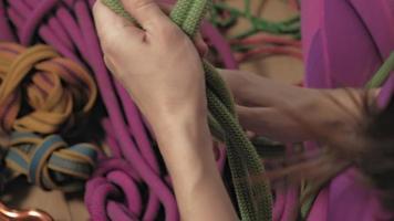 uma mulher com roupa térmica roxa tricota um nó de escalada figura oito video