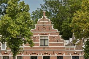 Trees along the road and in front of a typical dutch house in Vlissingen in Netherlands photo