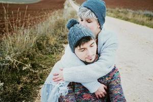 Pareja de jóvenes millennials abrazándose en un viaje de aventura en un camino rural al aire libre foto