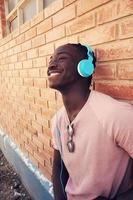 Young man leaning on brick wall wearing headphones photo