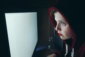 Joven mujer hacker delante de una pantalla de pc blanca foto