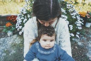 Mamá joven abrazando a su bebé y disfrutando de un día de primavera en el jardín. foto