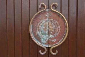 Medieval metal handle and doorknob on a wooden door photo