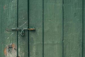El pestillo de la puerta vieja y oxidada y la cerradura de la puerta de madera verde foto