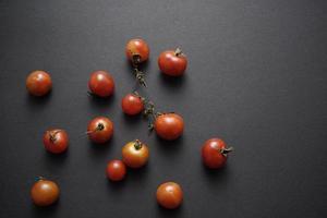Los tomates cherry planas yacían sobre fondo abstracto de textura grunge negro foto