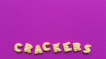 Crackers word on pink background Simple flat lay with pastel texture and copy space Stock photo