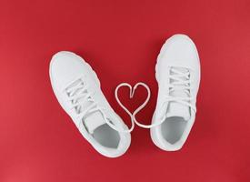 White sports shoes and heart shape from laces on a red background Simple flat lay photo