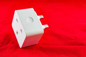 Toma de corriente inteligente wifi de color blanco sobre un fondo rojo. foto