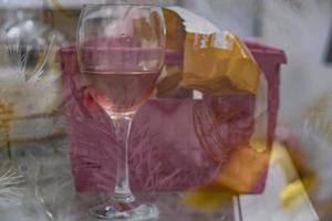 A glass of rose wine a gift box and white Christmas tree leaves double exposure suitable as a background photo