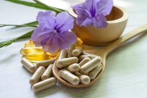 medicina alternativa cápsula orgánica a base de hierbas con vitamina e omega 3 aceite de pescado medicamento mineral con hojas de hierbas suplementos naturales para una vida sana y buena foto