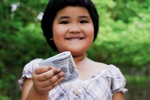 mano de niña asiática sosteniendo paquetes de dinero billetes de 100 dólares americanos foto