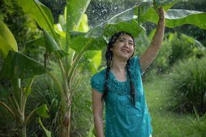 Retrato de una joven mujer asiática con cabello negro sosteniendo una hoja de plátano en la lluvia en el fondo del jardín verde foto