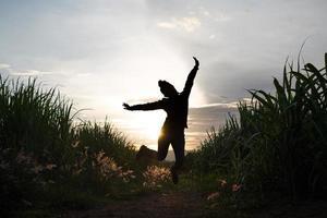 Granjero mujer silueta saltar en la plantación de caña de azúcar en el fondo atardecer atardecer foto