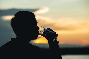 Silhouette man holding glass beer with sunset background photo