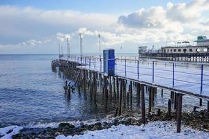 the old jetty is covered with snow by the sea in winter time photo