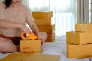 Young woman closed the parcel with masking tape while she was on the bed in her bedroom photo