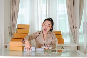 Business woman yawning counting money in office room photo