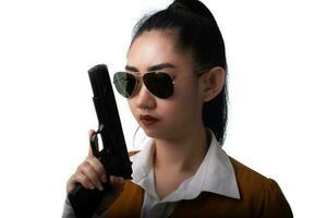 Retrato hermosa mujer asiática vistiendo un traje amarillo con una mano sosteniendo la pistola en el fondo blanco. foto