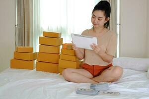 Asia joven está sentada en la cama con un ordenador portátil en su habitación foto